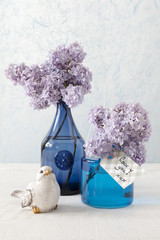 Lilacs in blue vases and a card with the words: Love you