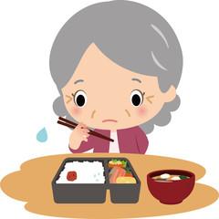 一人で食事をする高齢の女性
