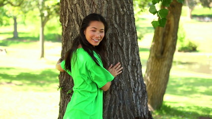 Happy environmental activist hugging a tree