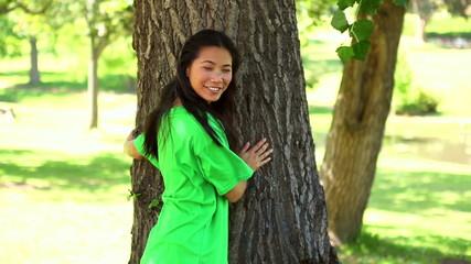 Happy environmental activist hugging a tree