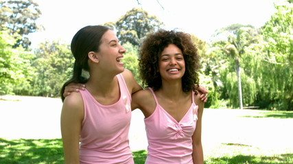 Two friends wearing pink for breast cancer in the park