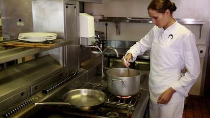 Pretty chef stirring a large pot