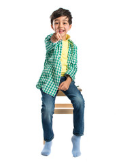 Boy pointing to the front on wooden chair over white background