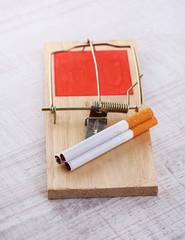 Mousetrap with cigarette, on wooden background