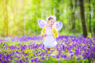 Pretty toddler girl in fairy costume in bluebell forest