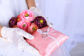 Bride in gloves holding wedding bouquet, and wedding rings