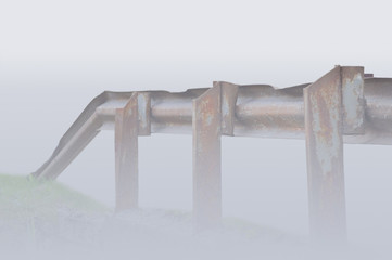 Old aged rusty grunge metallic bridge rail shoruded by mist