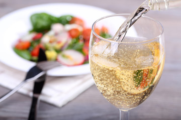Pouring white wine into glass and food background