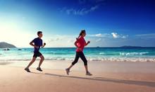 Homme et femmes courant sur la plage tropicale au coucher du soleil