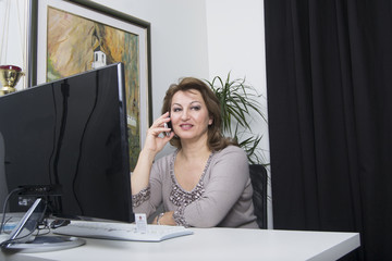 Woman talking on cell phone (office, computer, desktop)