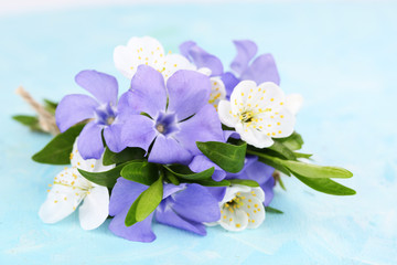 Beautiful bouquet with periwinkle flowers on blue table