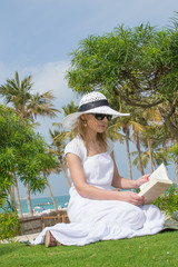 Sexy woman reading in the park next to the beach (Dubai, UAE)