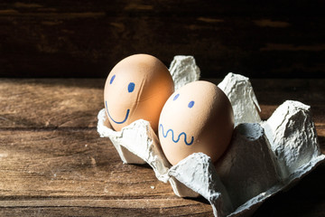 eggs in carton box on wooden background