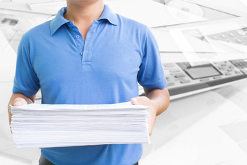 Man Carrying Pile Of Paperwork In Office