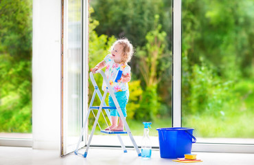 Cute girl washing a window with view garden
