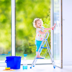 Pretty girl washing a window with view garden
