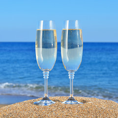 Two Glasses of champagne on a beach sand