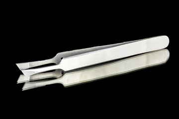 Metail tweezers on a black background