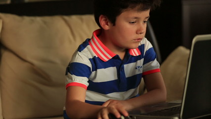 smart little child using laptop at home
