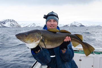 Happy angler with huge cod fish