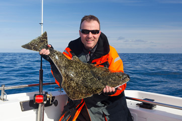 Happy angler with halibut fish