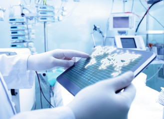 Doctor working with tablet PC and world map