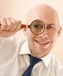 Young business man looking through magnifier