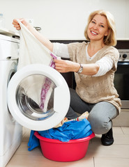 woman using washing machine at home laundry
