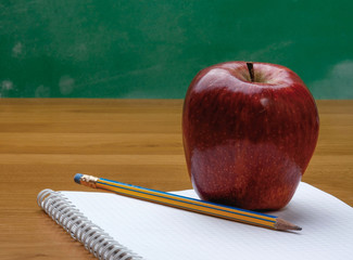 A red apple on a notebook.