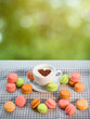 Colorful macaroons with cup of coffee with heart shape on the na