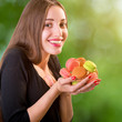 Young and smiling woman holding a bunch of colorful macaroons on