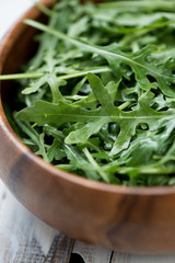 Fresh arugula in a wooden bowl, close-up, vertical shot