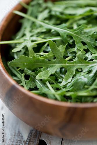 Fresh arugula in a wooden bowl, close-up, vertical shot