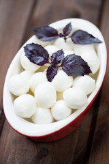 Mozzarella balls with purple basil in a glass bowl, studio shot