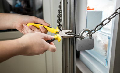 photo of woman trying to cut chain on fridge with pliers