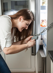 photo of woman trying to open lock hanging on fridge