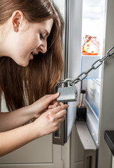angry woman opening chain on refrigerator with key