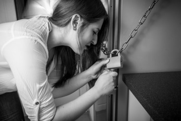 portrait of woman trying to open lock on fridge
