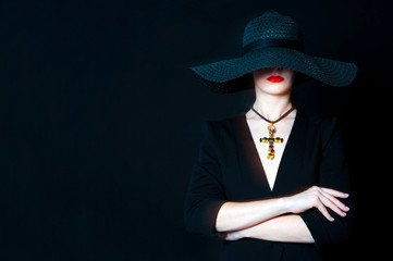 Beautiful young woman in black hat with jewel cross