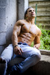 Muscular young man shirtless sitting against concrete wall