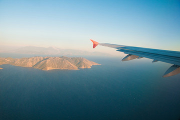 View from the airplane over the sea, the mountains, the wing