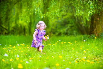Beautiful girl playing on meadow with dandelions