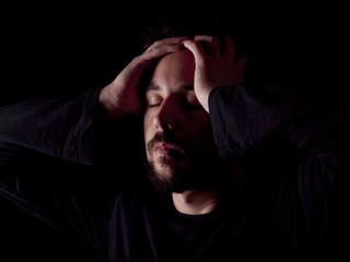 Low key image of a bearded man with a headache