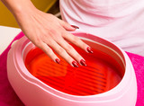 Female hand and orange paraffin wax in bowl.    poster