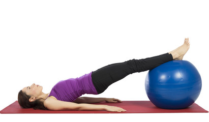 Young fitness woman working her abs with pilates ball