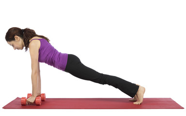 Woman lifting weights in plank pose
