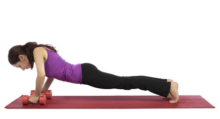 Woman in plank pose with dumbbells