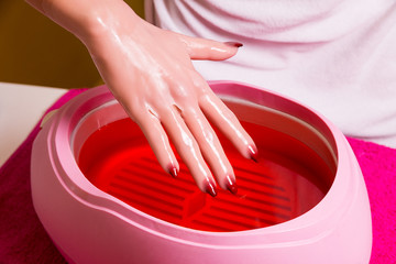 Female hand and orange paraffin wax in bowl.