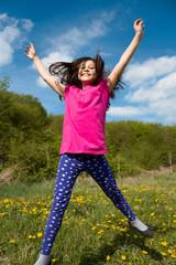 junges Maedchen springt vor Freude durch den Garten