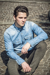 Attractive young man sitting on pavement outdoors